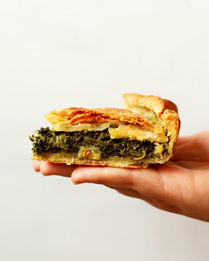 hand holding slice of spinach and cheese pie